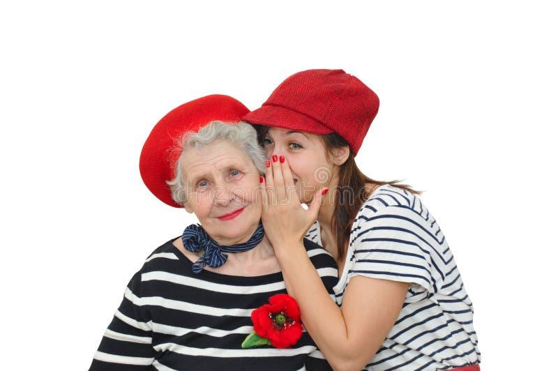 Großmutter und ihr Enkelinflüstern lizenzfreies stockbild