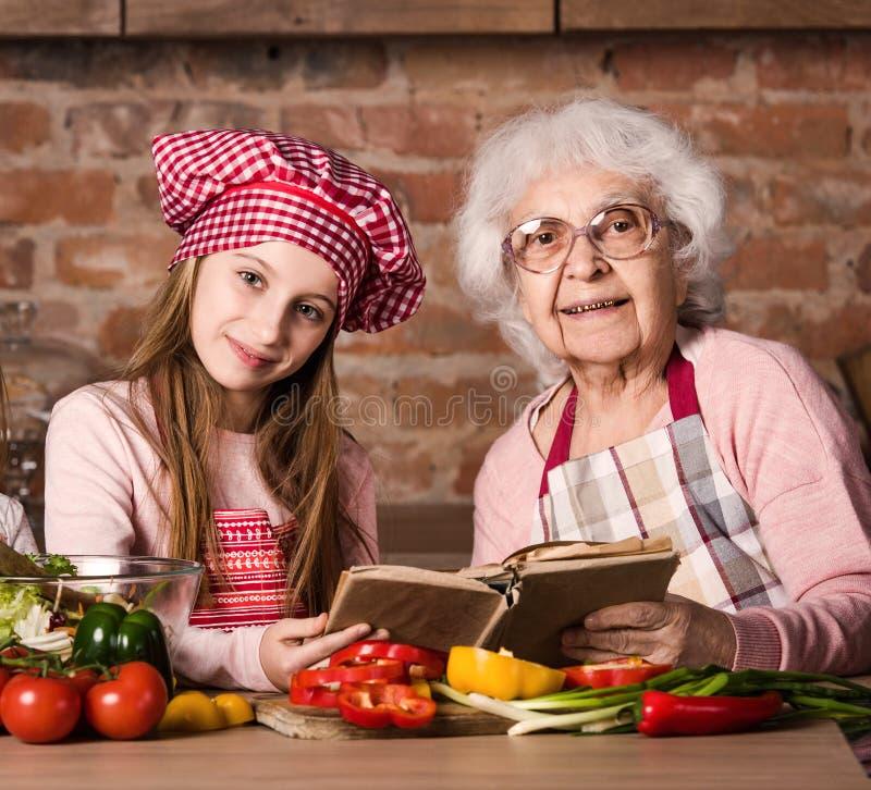 Großmutter und ihre Enkelin, die zusammen an der Küche sitzen stockbilder