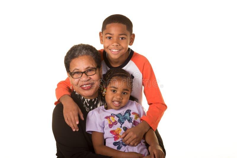 Großmutter und ihre Enkelkinder lokalisiert gegen einen weißen Hintergrund lizenzfreies stockbild