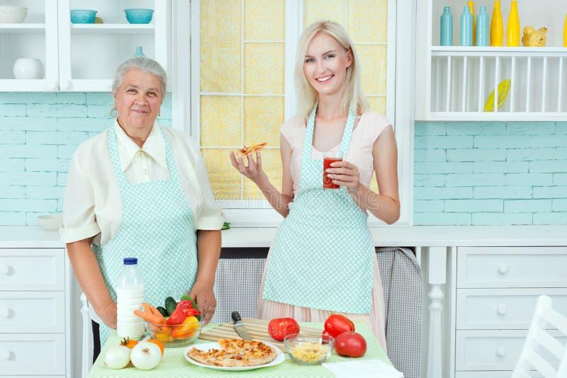 Großmutter und junge Frau, die Pizza essen stockfotos