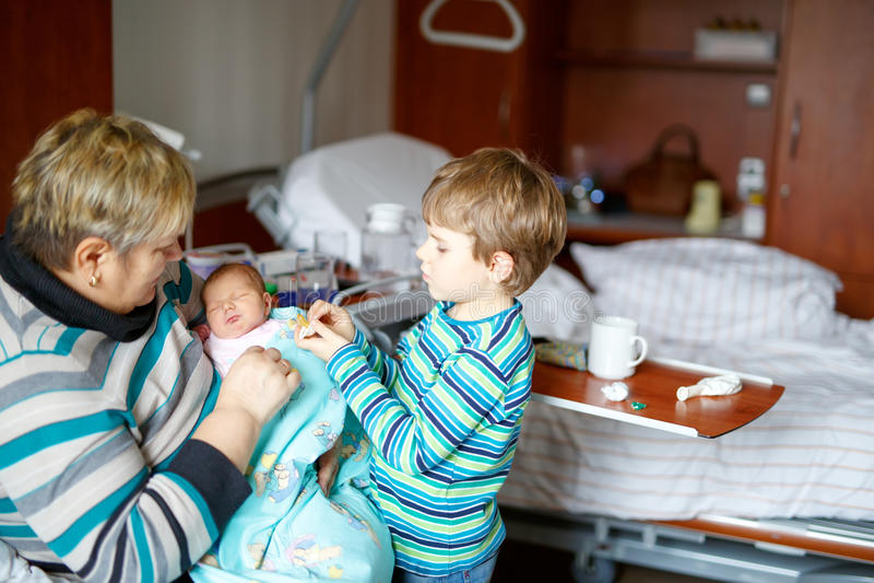 Großmutter- und Kinderjunge, der neugeborenes Babyenkelkind auf Armen hält lizenzfreies stockfoto