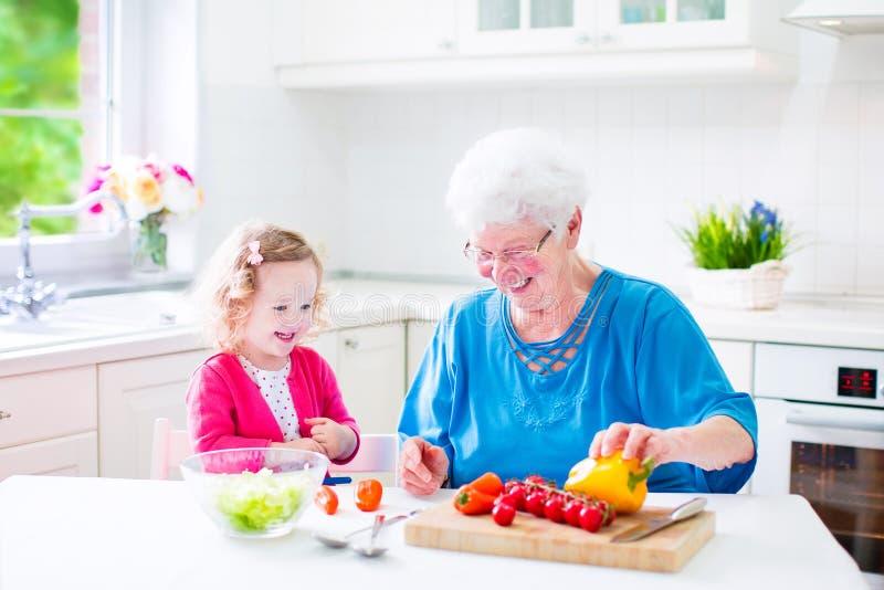 Großmutter und kleines Mädchen, die Salat machen lizenzfreie stockfotografie