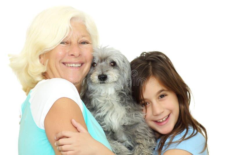 Großmutter und Mädchen, die den Familienhund umarmen lizenzfreie stockfotografie