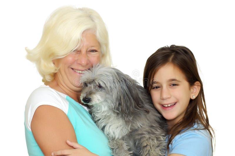 Großmutter und Mädchen, die den Familienhund umarmen stockfoto