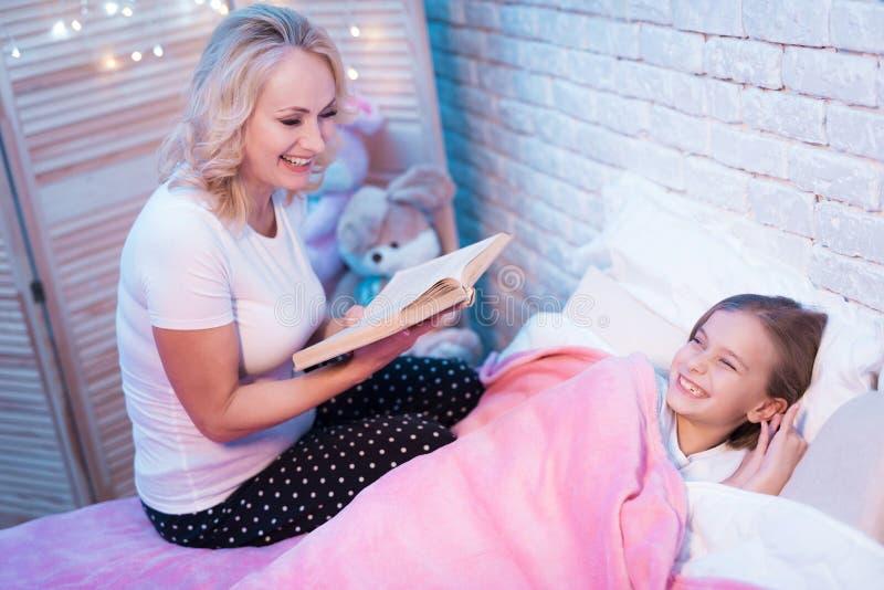 Großmutterlesebuch, während Enkelin nachts zu Hause liegt lizenzfreies stockfoto