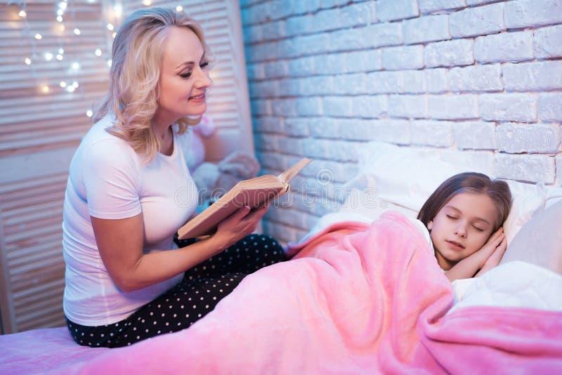 Großmutterlesebuch, während Enkelin nachts zu Hause liegt lizenzfreie stockfotos