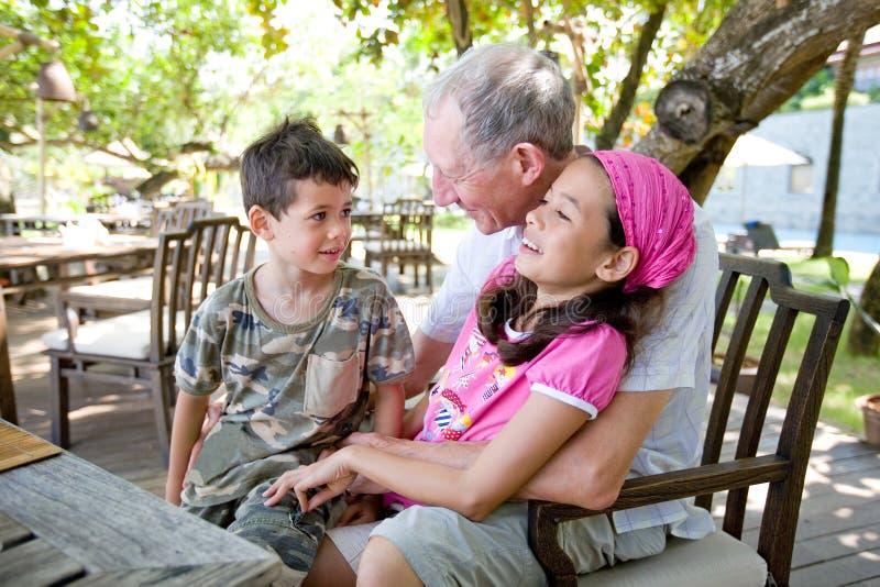 Großväterliche Ausgabenzeit mit Enkelkindern stockfotografie