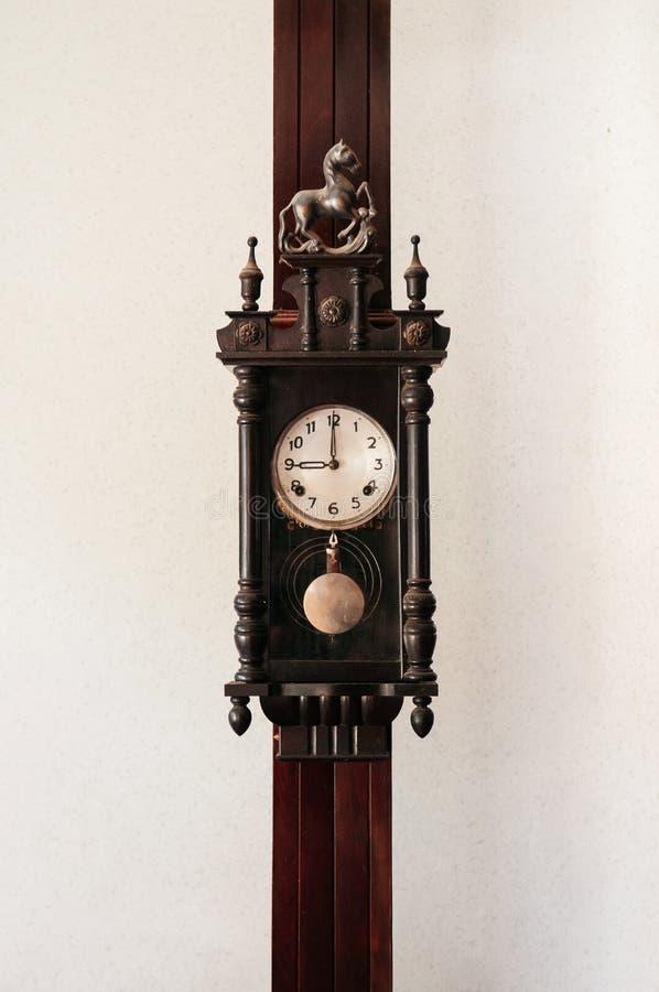 Großväterliche hölzerne Wanduhr der alten Weinlese, die an der hölzernen Säule hängt lizenzfreie stockfotos