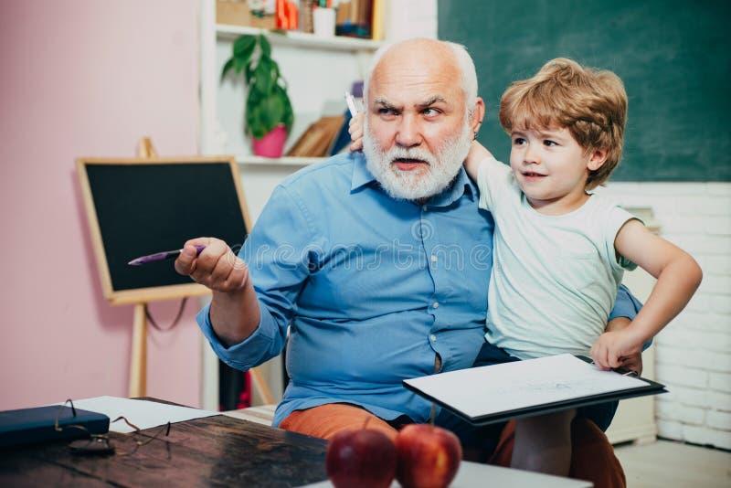 Großväterliche Unterhaltung mit Enkel Glücklicher netter kluger Junge und alter Tutor mit Buch Gro?vater und Enkel Konzept von stockfotos
