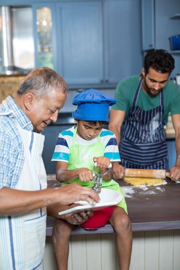 Großväterlicher darstellender Tablet-Computer zum Jungen bei der Zubereitung des Lebensmittels stockbilder