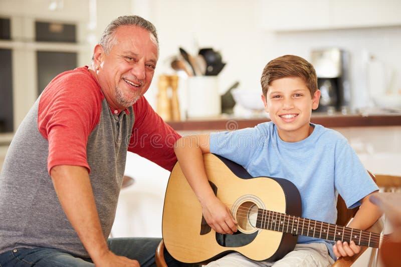 Großväterlicher unterrichtender Enkel, zum der Gitarre zu spielen stockbild
