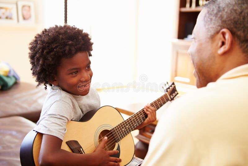 Großväterlicher unterrichtender Enkel, zum der Gitarre zu spielen stockfoto
