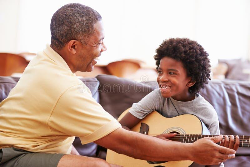 Großväterlicher unterrichtender Enkel, zum der Gitarre zu spielen stockfotografie