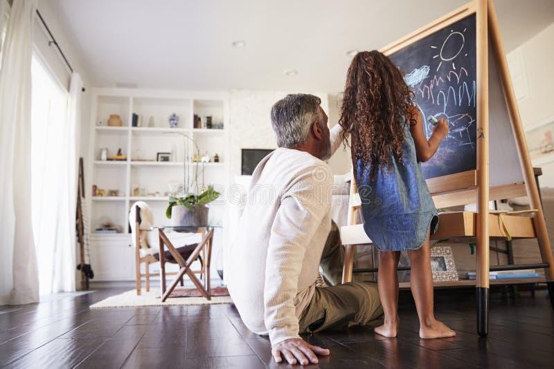 Großväterliches Sitzen auf der Bodenzeichnung auf einer Tafel mit seiner jungen Enkelin, niedriger Winkel stockfoto