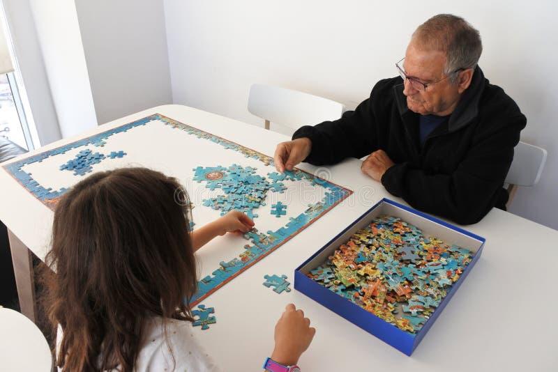 Großväterliches Spiel mit Enkelinpuzzlespiel lizenzfreie stockfotos