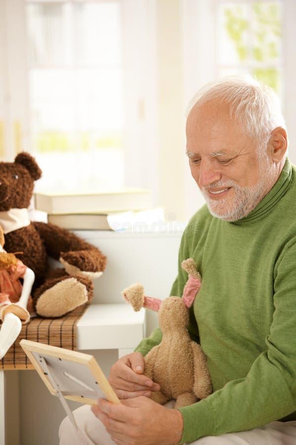 Großvater, der Enkelkindfoto betrachtet stockfoto