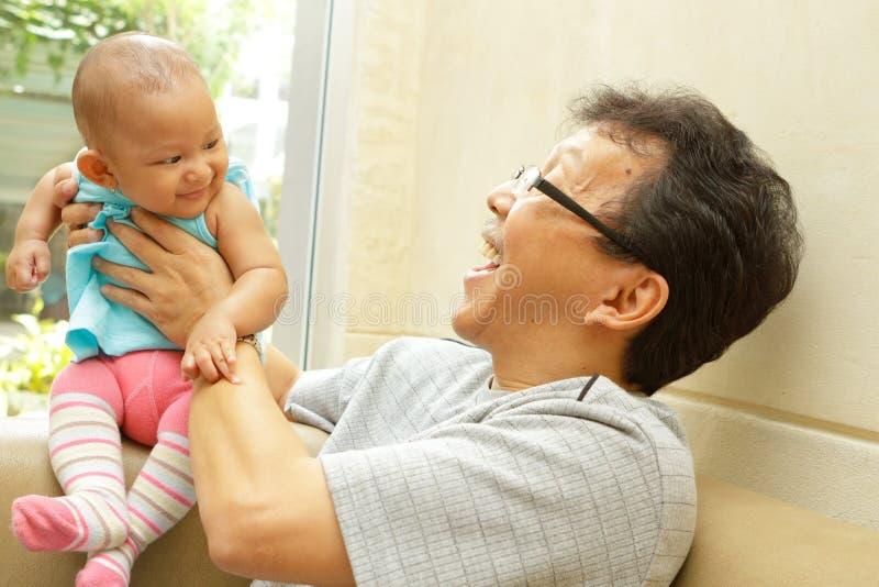 Großvater, der mit Schätzchenenkelin spielt lizenzfreies stockfoto