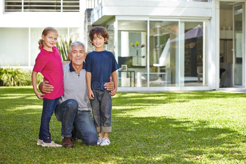 Großvater, der seine Enkelkinder im Garten umfasst stockfotografie