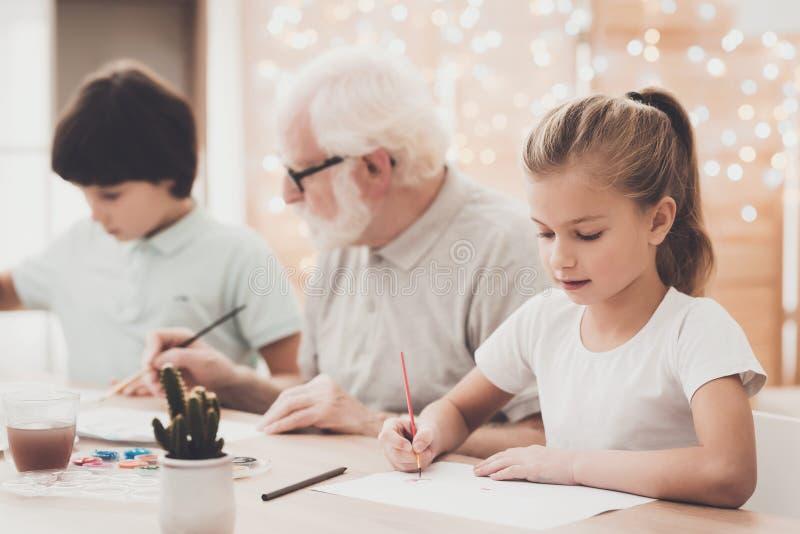 Großvater, Enkel und Enkelin zu Hause Großvater hilft Kinderfarbe lizenzfreies stockbild