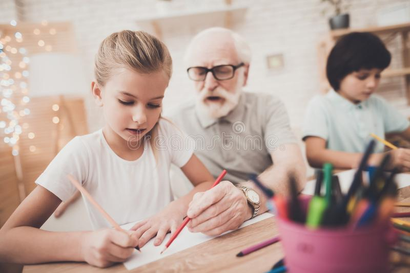 Großvater, Enkel und Enkelin zu Hause Kinder zeichnen lizenzfreies stockbild