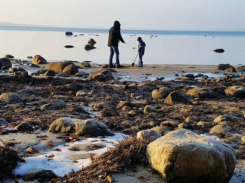 Großvater mit seinem Enkel am Strand stockfotografie