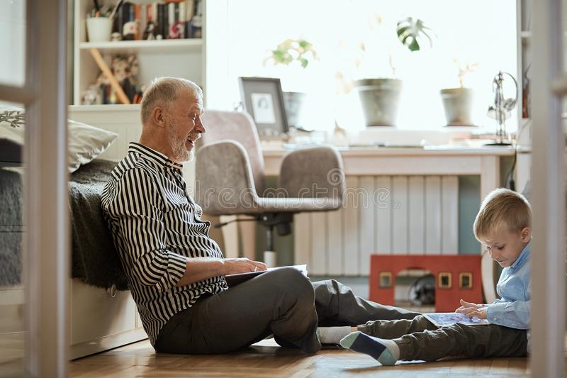 Großvater schaut Fotoalbum mit seiner Hochzeit, den kleinen Jungen, der elektronische Tablette verwendet lizenzfreie stockbilder