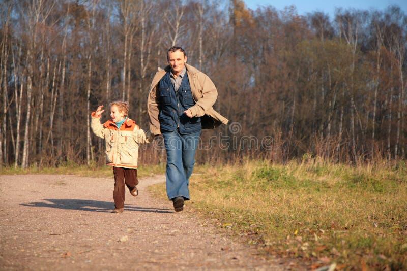 Großvater und der Enkel laufen gelassen auf Pfad stockbild