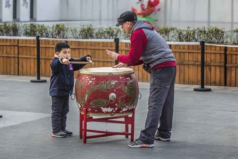 Großvater und Enkel, die Trommeln auf den Straßen von Konfuzius-Tempel spielen lizenzfreie stockfotografie