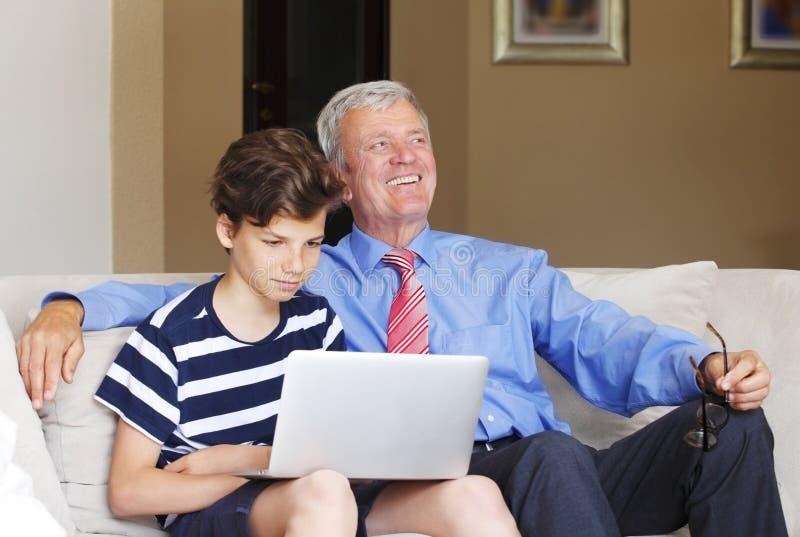 Großvater und Enkel mit Laptop lizenzfreie stockfotografie