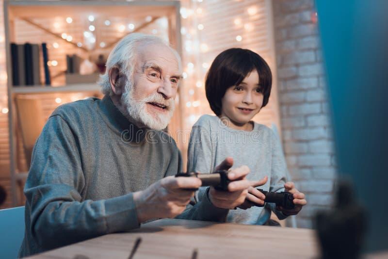 Großvater und Enkel spielen Videospiele auf Computer nachts zu Hause stockfotos