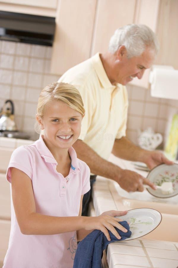 Großvater-und Enkelin-Reinigungs-Teller lizenzfreies stockbild