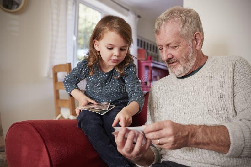 Großvater und Enkelin zu Hause, die Fotografien betrachten lizenzfreies stockbild