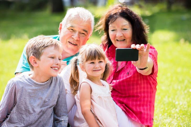 Großvater und Enkelkinder, die Foto im Park machen stockbild
