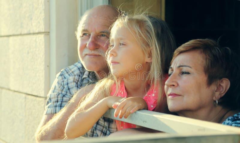 Großvater und Großmutter, die Enkelin halten stockbild