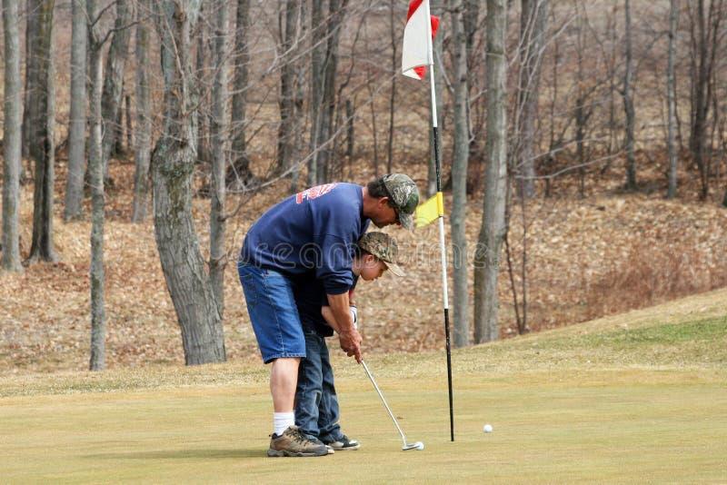 Großvater-unterrichtendes Enkel-Golf lizenzfreie stockfotos