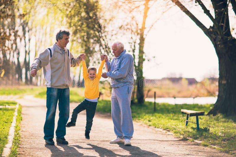 Großvater zwei, der mit dem Enkel geht stockfotos