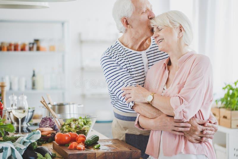 Großvaterumarmungen und lächelnde Großmutter der Küsse lizenzfreies stockbild