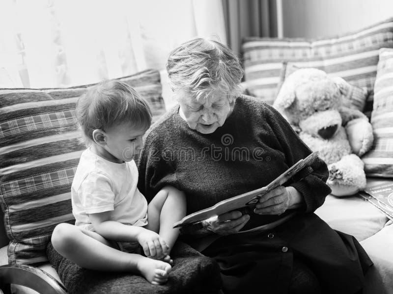 Groß-großartige Mutter liest ein Buch zu wenigem Jungen stockfoto