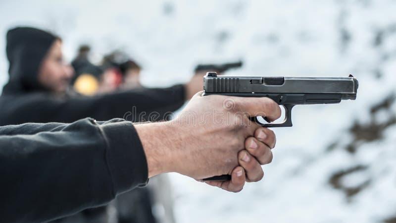 Großaufnahme des tireurpraxis-Pistolenschießens in der Reihengruppe stockfotos