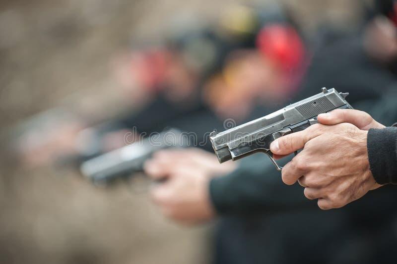 Großaufnahme des tireurpraxis-Pistolenschießens in der Reihengruppe stockbilder