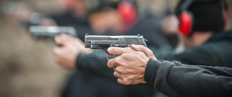 Großaufnahme des tireurpraxis-Pistolenschießens in der Reihengruppe lizenzfreie stockfotos