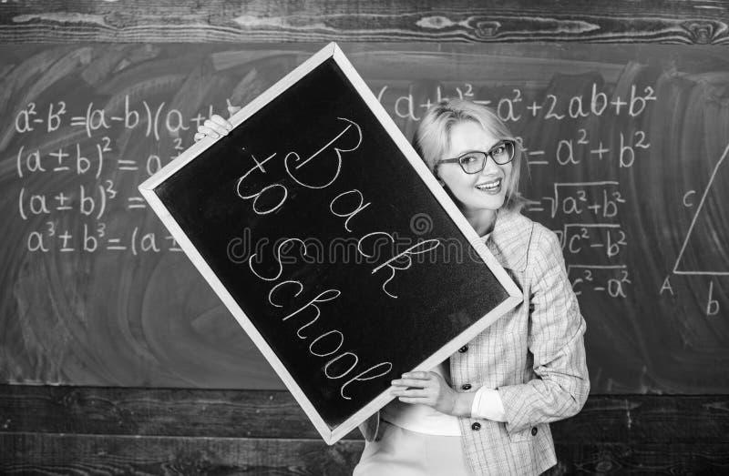 Großer Anfang des Schuljahres Spitzenweisen, Studenten zurück zu Schule zu begrüßen Lehrerfrauengriff-Tafelaufschrift lizenzfreie stockfotografie