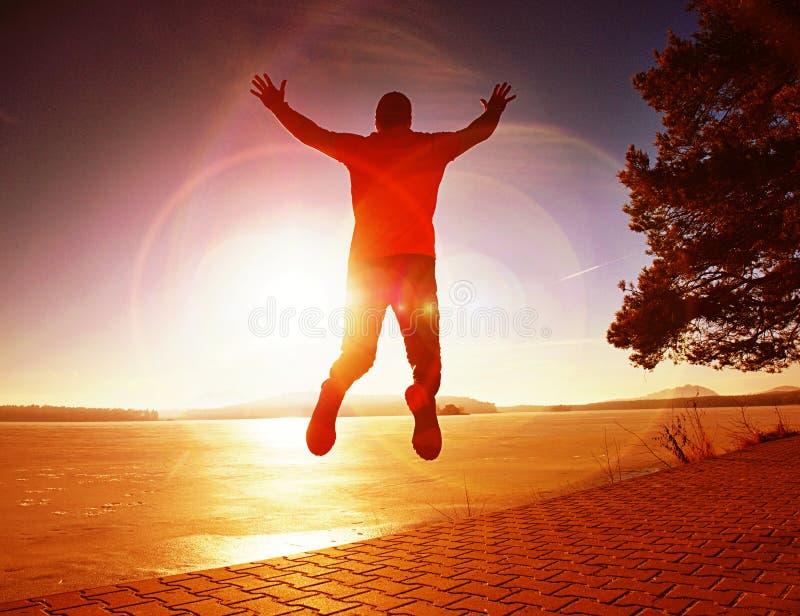 Großer Mann, der durch Meer auf dem Strand jamping ist Leistungsfähiger Läufer lizenzfreies stockbild