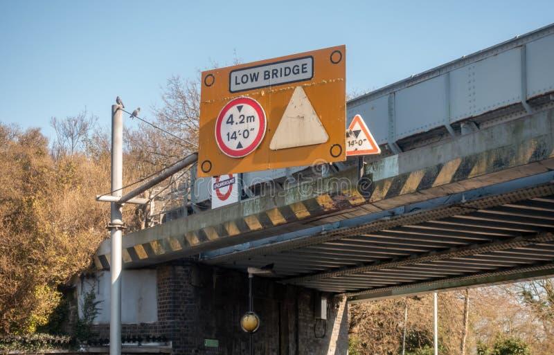 Großes gelbes niedriges Brückenzeichen auf einer Eisenbahnbrücke, Warnen der Höhenbeschränkung stockbilder