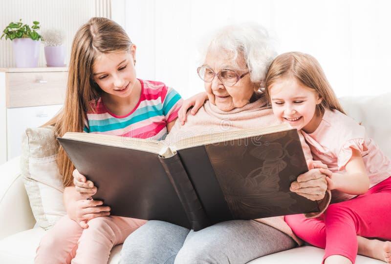 Großmutter mit Enkelinlesebuch lizenzfreies stockbild
