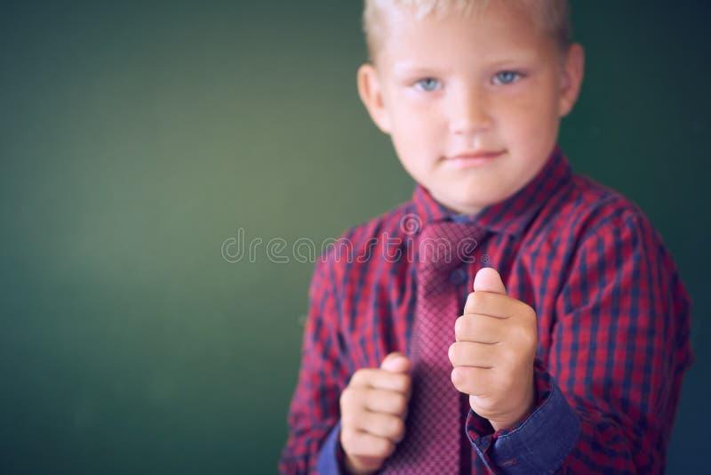Groźna 5-letni stara chłopiec patrzeje gwałtowny z pięściami w przodzie, postępuje jak łobuz troszkę przy szkołą, kontrast obraz stock