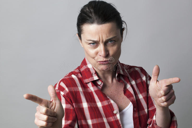 Groźna w średnim wieku kobieta prowokuje z agresywnymi ręka gestami zdjęcia royalty free