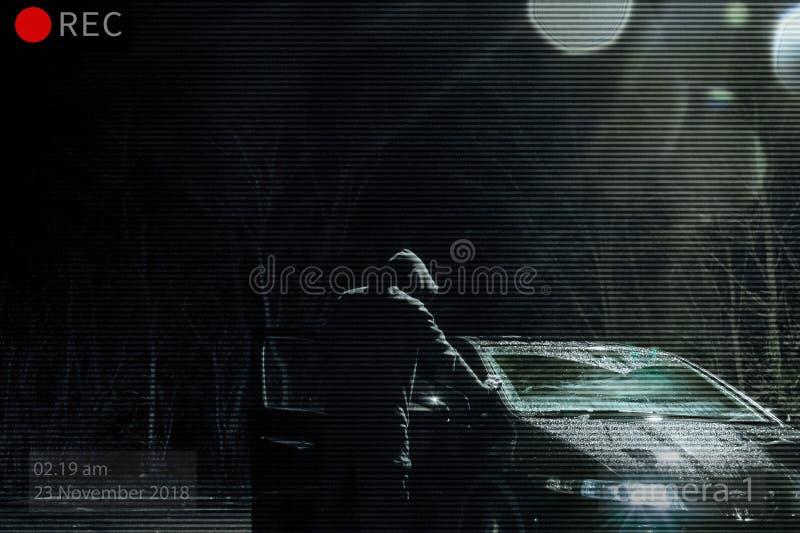Grożenie okapturzał mężczyzny patrzeje w samochód przy nocą Photoshop redaguje patrzeć jak CCTV wizerunek zdjęcia royalty free