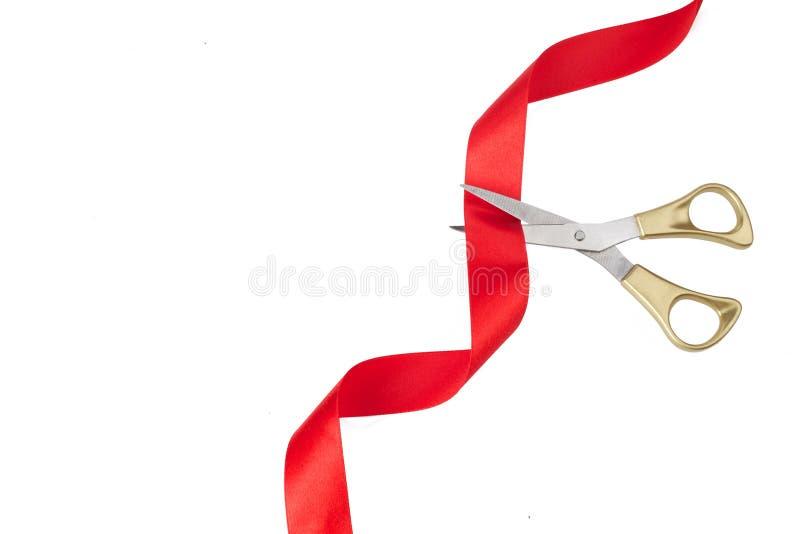 Gro?artige ?ffnung Draufsicht von den Goldscheren, die rotes Band auf wite Hintergrund schneiden lizenzfreie stockfotografie