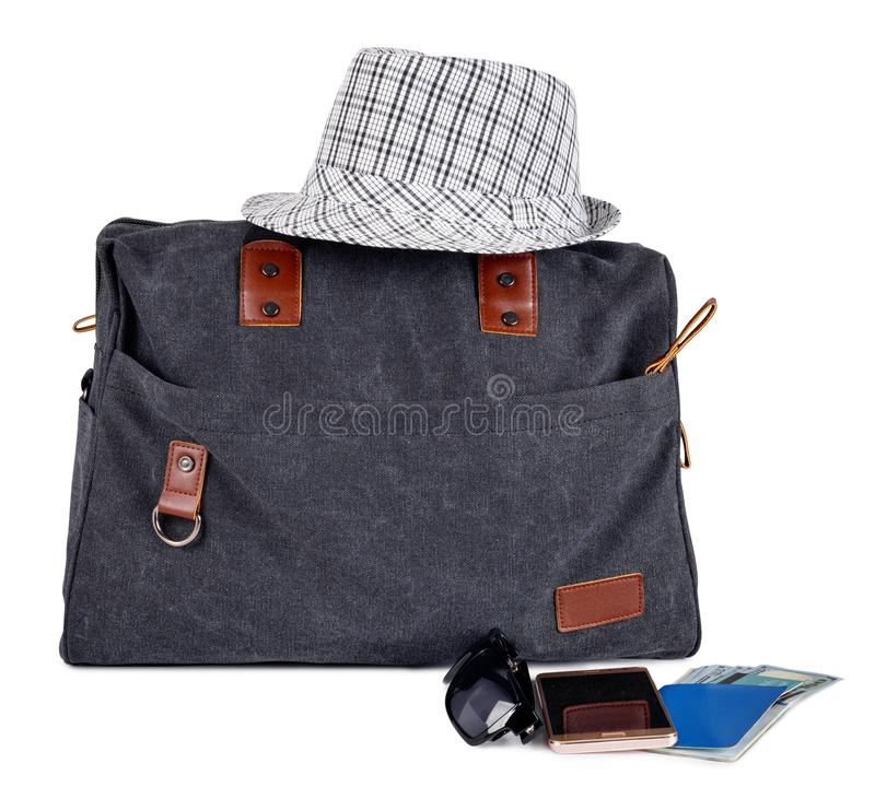 Gro?e schwarze stilvolle Reisetasche f?r Reise mit Hut, P?ssen und Geld auf wei?em Hintergrund lizenzfreie stockfotografie